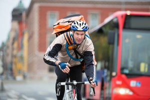 Young male cyclist with courier delivery bag riding bicycle on s